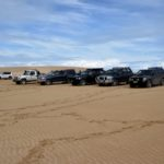 Vehicle convoy on sand dune overlooking Lake Bonney